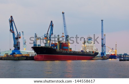 A container ship in a container terminal in the harbor of Hamburg, Germany. - stock photo