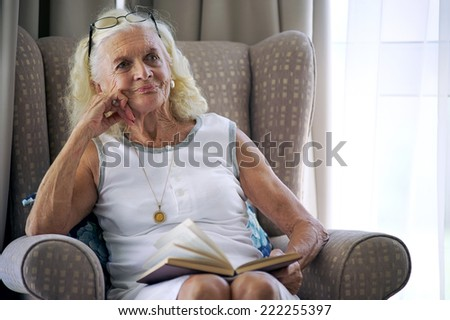 A content elderly woman sitting on her sofa with a book in her lap - stock photo