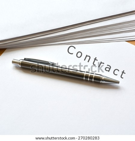 A contract and a pen lying on a table - stock photo