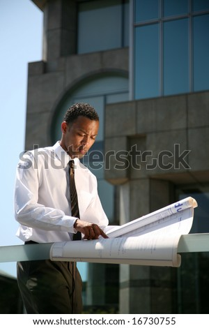 a contractor reviews his latest buildings blue prints - stock photo