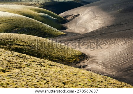 A contrasty wavy landscape of a former brook where black volcanic dunes meet green dunes covered by moss. Lakagigar volcanic area, Iceland. Sunset time - stock photo