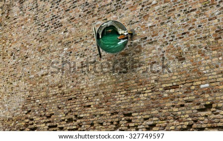 A convex mirror on the brick wall of a canal-side building in Venice, italy. - stock photo