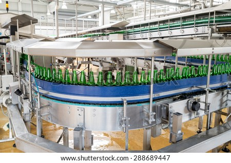 A conveyer belt with empty bottles for beer is seen during production process in a brewery. - stock photo