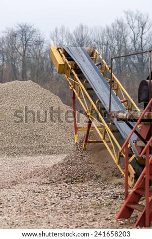 A conveyor belt at a gravel heap. - stock photo