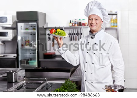 A cook prepares in the kitchen - stock photo