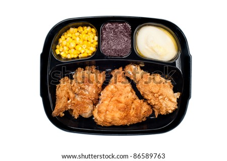 A cooked tv dinner of fried chicken, corn, mashed potatoes and dessert in a plastic black tray. - stock photo