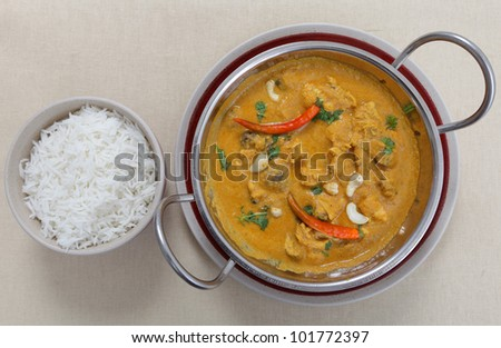 A cooking pan full of chicken and mushroom curry with a cashew nut sauce, garnished with cashews, coriander and chillies with a bowl of rice from above. - stock photo