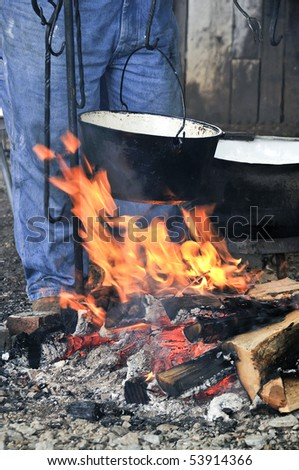 A cooking pot over a flaming campfire - stock photo
