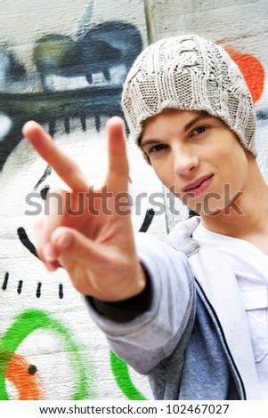 a cool-looking young man in front of graffiti - stock photo
