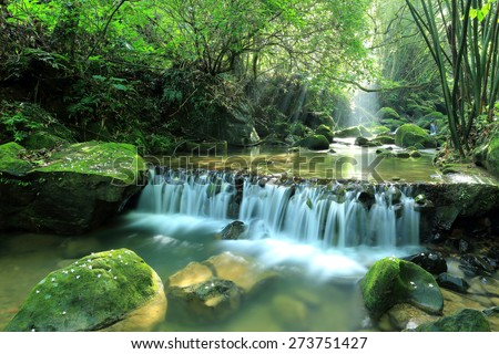 A cool refreshing waterfall hidden in a mysterious forest of lush greenery ~ Beautiful river scenery of Taiwan in springtime - stock photo