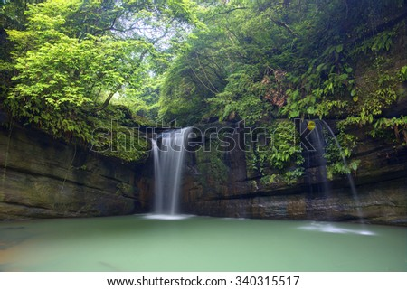 A cool refreshing waterfall pouring into an emerald pond hidden in a mysterious forest of lush greenery ~ Beautiful river scenery of Taiwan in springtime - stock photo