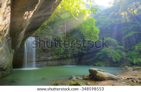 A cool refreshing waterfall pouring into an emerald pond hidden in a mysterious forest of lush greenery ~ Beautiful river scenery of Taiwan (Bright spring version)  - stock photo