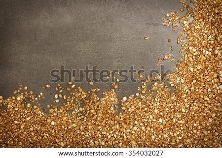 A corner of Gold nugget grains, on cement background - stock photo