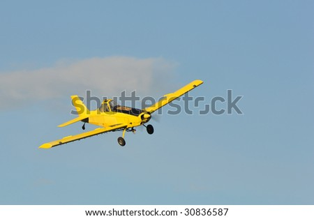 A corp duster or agricultural aircraft flying in a blue sky - stock photo