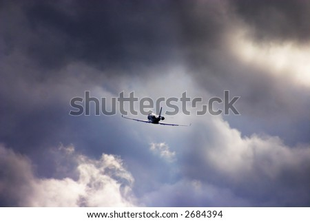 A corporate jet climbs into the clouds after takeoff. - stock photo