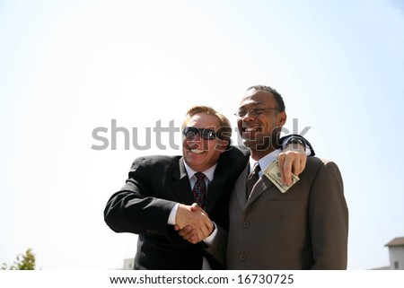 a corrupt politician takes a bribe from a scheming business man while posing for a photo op - stock photo