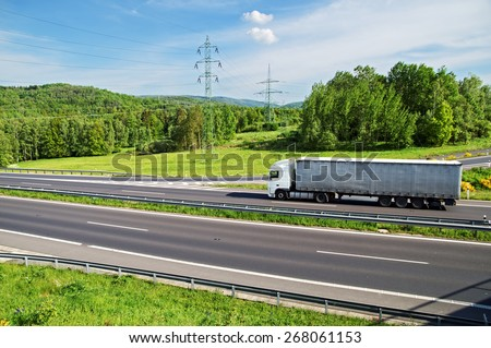 A country landscape with highway and ride the truck. Despite the highway leading power lines to pylons of electric power lines. View from above. - stock photo