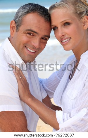 a couple behind the sea : a muscular 40 years old man and a 35 years old blonde woman - stock photo