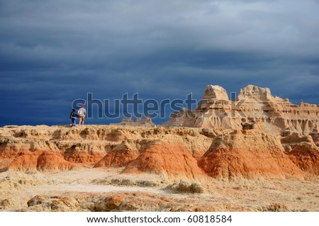 A couple climbing the red rock at Badlands, South Dakota, when storm is coming - stock photo