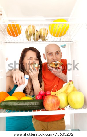 A couple eating cream cakes standing in the open door of the refrigerator full of healthy fresh fruit. - stock photo