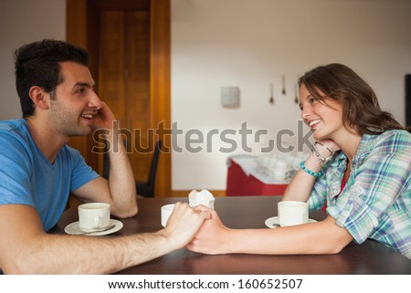 A couple holding hands and looking at each other in college canteen - stock photo