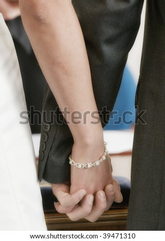 A couple holding hands as they get married - stock photo