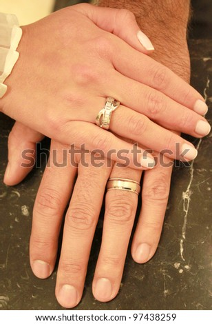 A couple holding hands together with their rings showing - stock photo