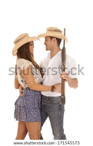 A couple holding onto each other while he is holding onto a gun. - stock photo