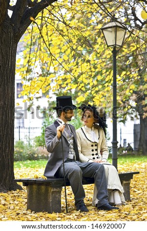 A couple in love, dressed in the style in the end of the 19th century, sitting on a park bench in fall. - stock photo