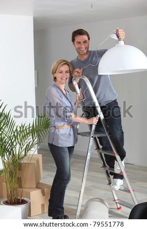 A couple installing a lamp in their new home. - stock photo