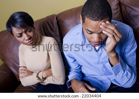 A couple is having an argument on a couch and the man is frustrated or feeling guilty - stock photo