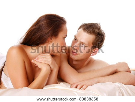 A couple is lying in bed and looking to each other - stock photo