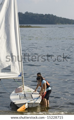 A couple is standing in the lake water next to their sailboat.  They are getting ready to take their boat sailing.  Vertically framed shot. - stock photo