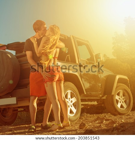 A couple kissing next to a 4x4 car on sunset - stock photo