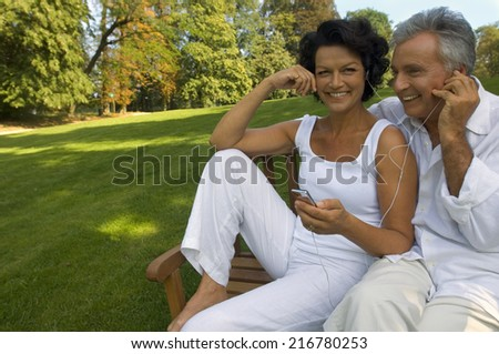 A couple listening to their music player. - stock photo