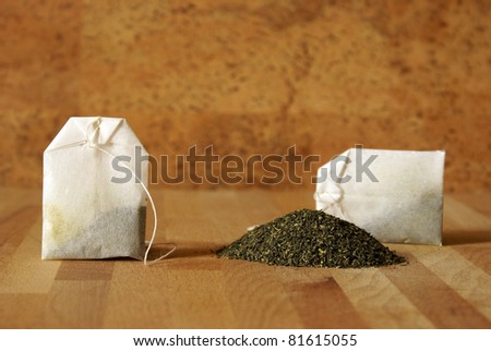 A couple of bags are next to a pile of green tea leaves. - stock photo