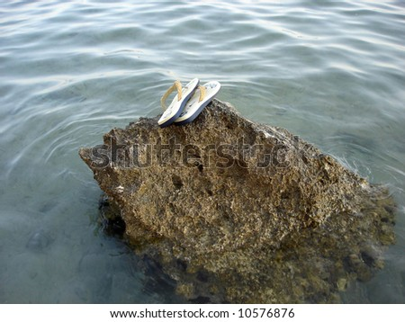 a couple of beach shoes on coral-reef left for hope to return - stock photo