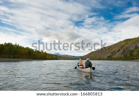 A couple of canoeists on wilderness adventure trip paddling wide Pelly River, central Yukon Territory, Canada - stock photo