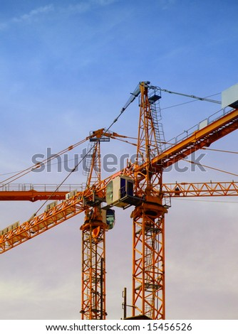 a couple of cranes on a construction site with a blue sky backdrop - stock photo