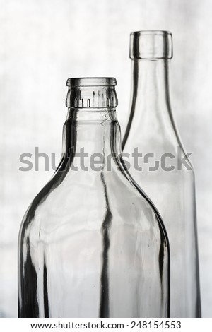 A couple of empty crystal bottles against a clear background - stock photo