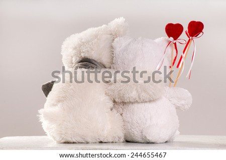 A couple of teddy bears with plush hearts - stock photo