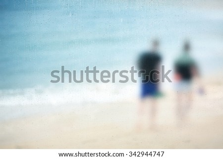 A couple of tourist walking on the beach ( koh samui - Thailand )during rain fall,View through the window with shallow depth of field composition. - stock photo