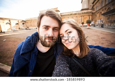 A couple of tourists - handsome man and a beautiful young woman - take selfie while traveling in Rome, Italy - stock photo