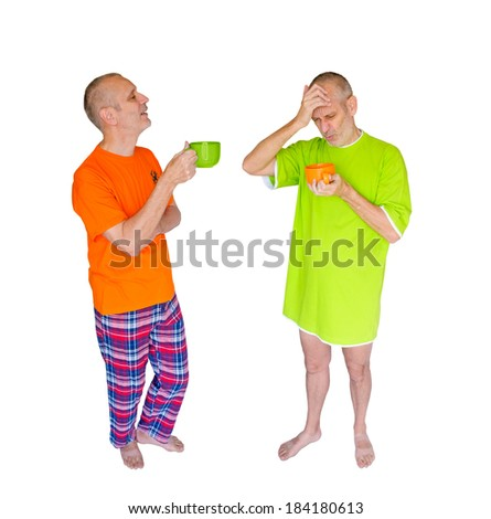 A couple of twin men drinking coffee after waking up. One is in green nightdress, holding an orange cup, the other is in pajamas with an orange T-shirt, and is holding a green cup - stock photo