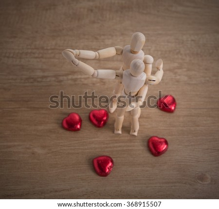 A couple of wooden doll man on valentine days showing love to each other and focus either on heart-shaped chocolate and the couple - stock photo