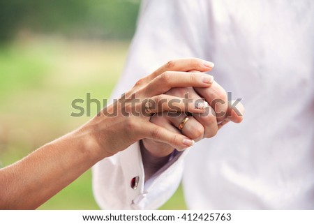 a couple of young lovers strolling holding hands in a park, close up of the hands - stock photo