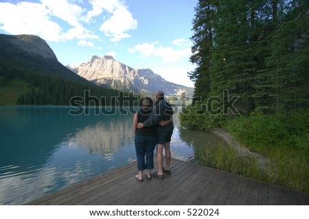 A couple on a dock in the mountains by emerald lake in alberta canada. - stock photo