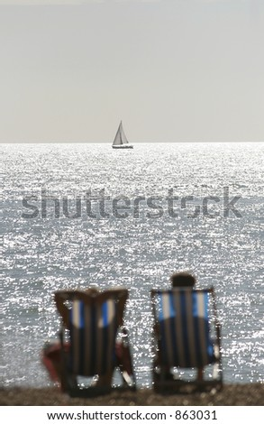 A couple on an English beach seated in deck chairs look towards a boat in focus on the horizon - stock photo