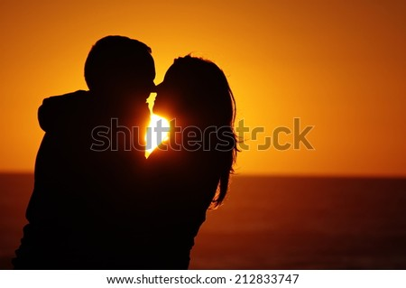 A couple on the beach with sunset background - stock photo
