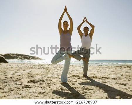 A couple performing yoga on a beach. - stock photo